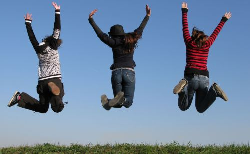 Three girlfriends leaping up in joy in open field