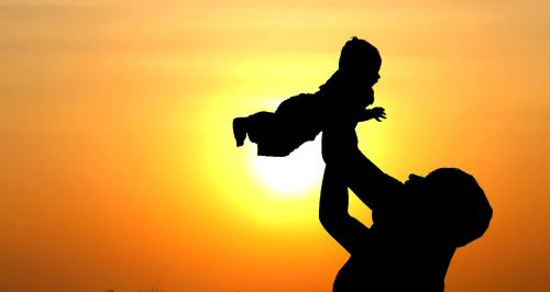 A mom holding a baby high up in the air against a sunset backdrop